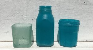 image of plain glass jars sprayed with sea glass spray paint in blue and aqua colors