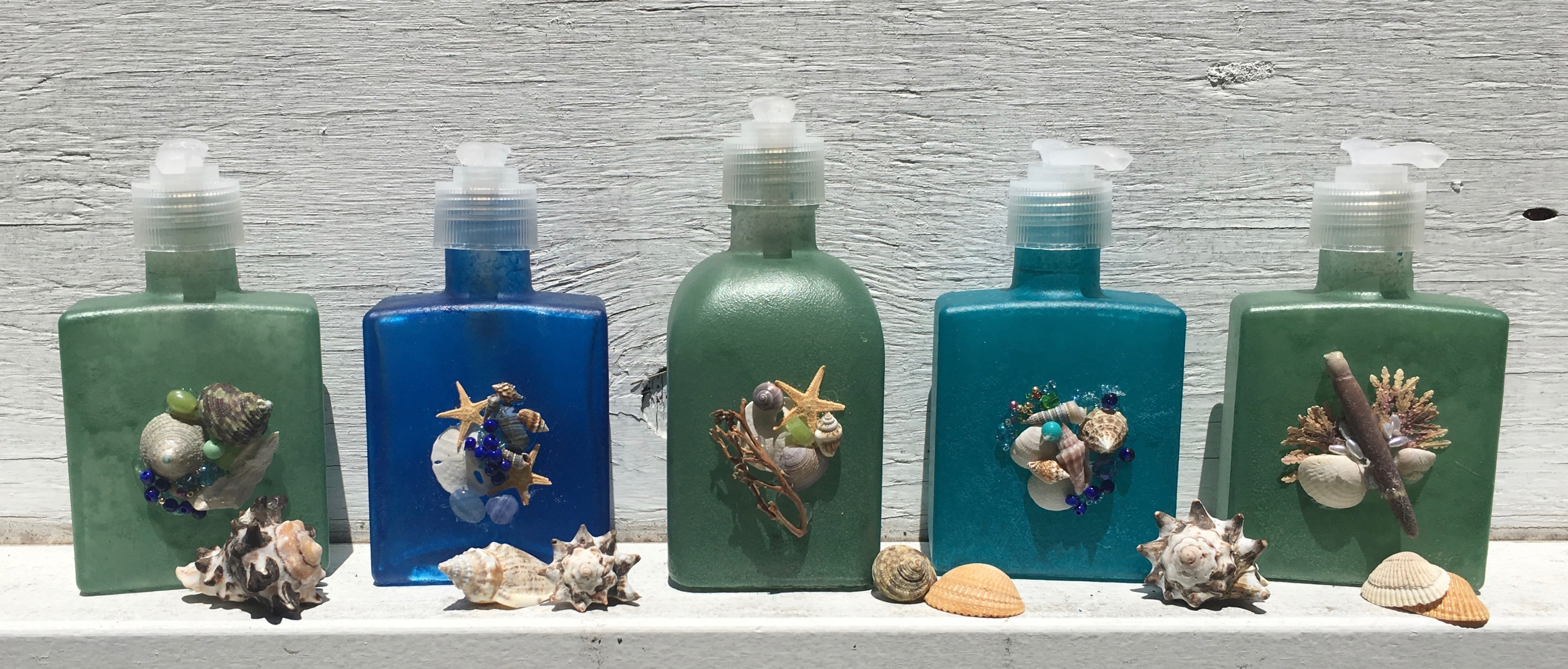 image of sea glass colored soap and lotion dispensers decorated with seashells and beads